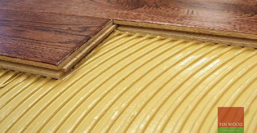 Which adhesive is recommended for gluing down a hardwood floor?